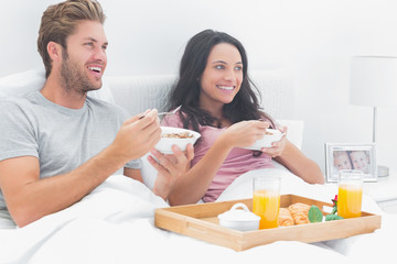 Beautiful couple eating cereal for breakfast