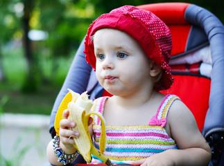 baby sitting in a pram eating banana