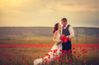 The bride and groom in a poppy field