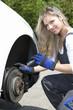 Frau überprüft die Bremsscheiben und Bremsklötze am Auto
