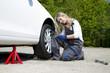 Blonde Frau schraubt das Rad wieder an den Wagen