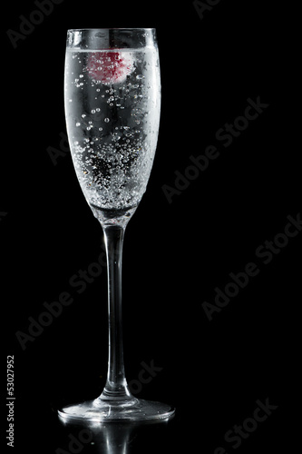 clear champagne with a raspberry
