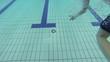 Kind taucht und holt Ring aus dem Wasser