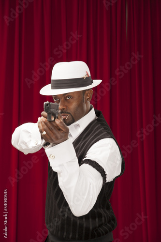 African American male in retro mobster suit holding a gun