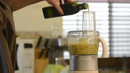 Blending Asian ingredients in a food processor adding olive oil
