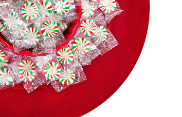 Peppermint Christmas candies on red plate over white