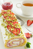 Strawberry roll with cream and pistachios.