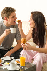 Carefree couple eating breakfast in pajamas