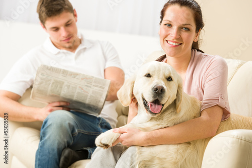 Resting joyful couple sitting and petting dog