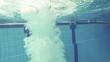 Junge springt in den Pool, Unterwasseraufnahme, Zeitlupe
