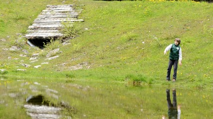child throws a stone in the pond