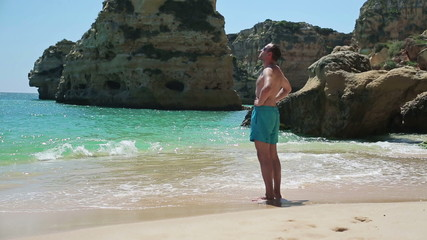 Young handsome man standing on beautiful beach