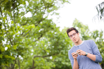 Young Student Using Smamrt Phone In The Park