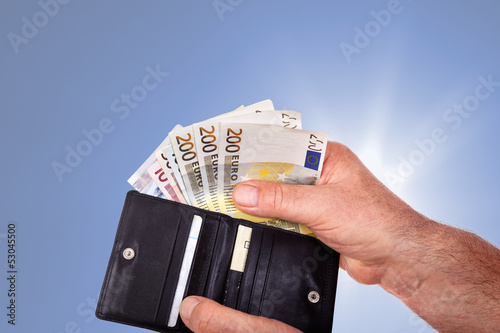 Hand with banknotes and wallet