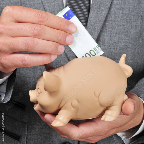 man in suit introducing a euro bill in a piggy bank