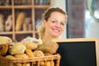 freundliche bäckereiverkäuferin mit hinweisschild