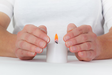 Women hands protect candlelight