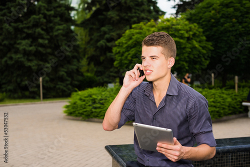 Businessman working on his tablet and talking on the phone