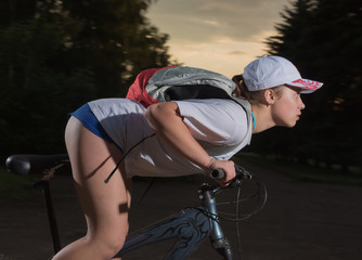 The girl goes on a bicycle in the evening