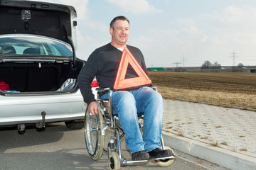 Man in a wheelchair and warning triangle next to his car
