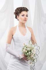 A young and beautiful bride standing with flowers