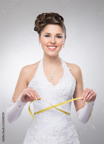 A young and beautiful bride measures her waist