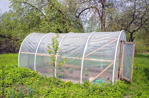 primitive plastic greenhouse in farm garden