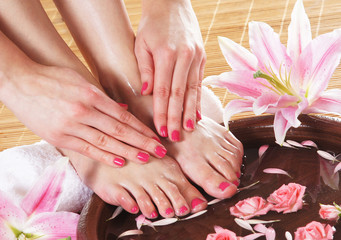 Spa background with beautiful feet, flowers and a ceramic bowl