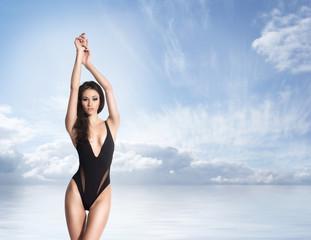 Beautiful girl in fashion swimsuit posing on the beach