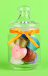 Glass jar containing various colored ribbons on green