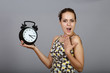 Surprised woman with alarm clock in studio at gray background
