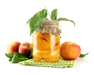 Jar of canned peaches and fresh peaches, isolated on white