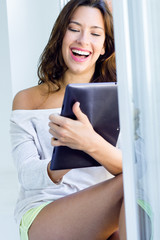 Beautiful woman at home using a digital tablet