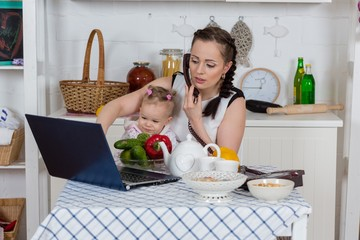 Mother with baby in kitchen.
