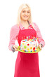 Blond female chef in apron holding a delicious cake
