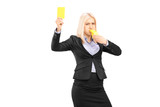 Angry businesswoman blowing a whistle and showing a yellow card