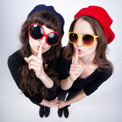 two cute girls showing quiet with their fingers cross their lips