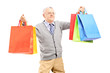 Smiling mature gentleman holding shopping bags and posing