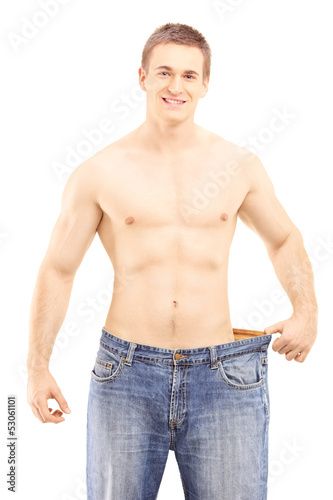 Shirtless smiling male showing his lost weight by putting on an