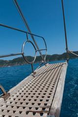 Ein hölzerner Badesteg auf einer Yacht mit Blick auf das Meer