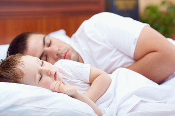 father and baby sleeping peacefully in bed