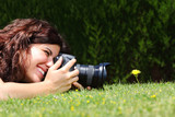 Beautiful woman taking a photography of a flower on the grass poster