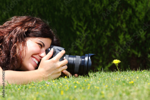 Beautiful woman taking a photography of a flower on the grass - 53062301