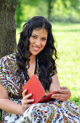 Portrait of beautiful girl reading book outdoors
