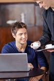 Kellner in Café bringt Tasse Kaffee