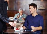 Kellner bringt Mann einen Cocktail