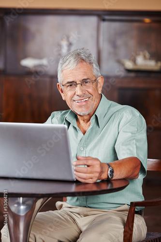 Lächelnder Senior am Laptop im Café