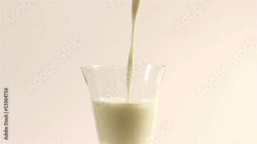 Milk flowing in a white transparent cup. Close up