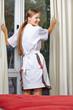 Zimmermädchen zieht Vorhänge auf