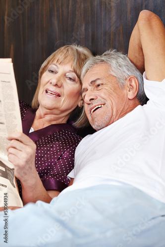 Senioren lesen Zeitung im Bett